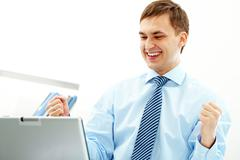 portrait of happy businessman expressing triumph in front of laptop - stock photo