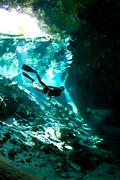 free diver at an entrance to cenote - stock photo