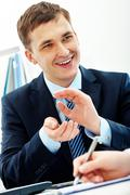 smart businessman explaining something to his colleague in office - stock photo