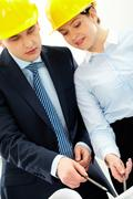 portrait of two architects in helmets discussing document at meeting - stock photo