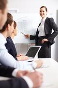 a businesswoman pointing at whiteboard before her colleagues - stock photo