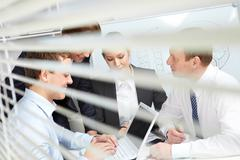 four working businesspeople viewed from the blinds - stock photo