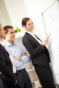 A businesswoman showing a scheme on a whiteboard to her colleagues Stock Photos
