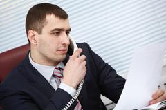 A manager with documents talking on the phone Stock Photos