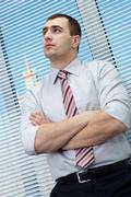 portrait of a serious manager standing with hands crossed on chest - stock photo