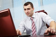 portrait of a young manager working with computer - stock photo