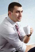portrait of a happy manager drinking coffee - stock photo