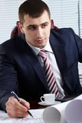 Portrait of handsome businessman looking at a laptop and making notes Stock Photos