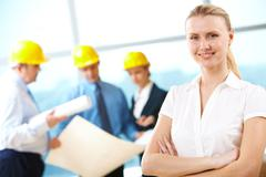Portrait of beautiful architect folding arms on the background of workers Stock Photos