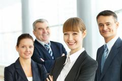a young businesswoman smiling against her three partners - stock photo