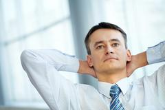 portrait of a serious mature businessman sitting with his hands behind head - stock photo