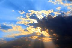 storm clouds and sun behind - stock photo