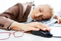 A young businesswoman sleeping on keyboard with a computer mouse Stock Photos