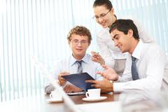 three business people discussing papers with current results - stock photo