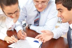 Three business people examining documents Stock Photos