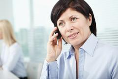 Mature businesswoman speaking on cellular phone Stock Photos