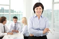 mature businesswoman looking at camera in working environment - stock photo
