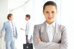 portrait of an attractive woman against her male colleagues - stock photo