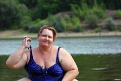 plump woman sitting near river - stock photo