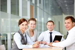 A business team of four sitting at table and looking at camera Stock Photos