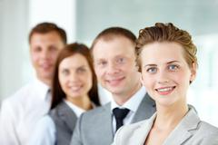 Portrait of friendly leader looking at camera with three employees behind Stock Photos