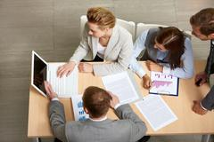 Image of business partners sitting at table and planning work Stock Photos