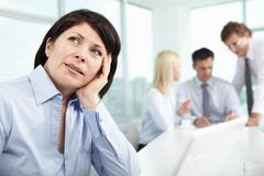 mature businesswoman at workplace thinking about something in working environmen - stock photo