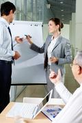 A business man and his partner standing by whiteboard and interacting Stock Photos