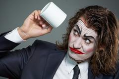 Portrait of businessman with painted face looking at coffee cup Stock Photos