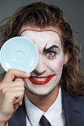 Portrait of businessman with painted face holding a saucer Stock Photos