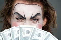 painted face behind several banknotes - stock photo