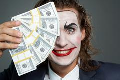 portrait of man with painted face holding banknotes - stock photo