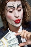 portrait of man with painted face with paper currency - stock photo