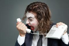 portrait of businessman with theatrical makeup shouting at telephone receiver - stock photo