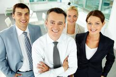 portrait of business partners looking at camera with their leader in front - stock photo
