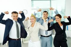portrait of business partners posing in front of camera showing their strength - stock photo