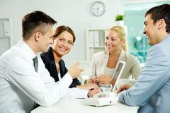 Four business partners sitting in office and interacting at meeting Stock Photos
