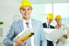 a smiling architect in helmet with two colleagues working on background - stock photo