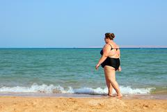 overweight woman walking on beach - stock photo