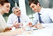 Three business partners sitting in office and planning work Stock Photos