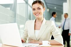 a beautiful businesswoman looking at camera with handshaking men on background - stock photo