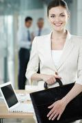 Portrait of a pretty businesswoman with briefcase looking at camera and smiling Stock Photos