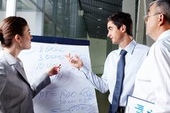 a business man and his partner discussing something on a whiteboard - stock photo