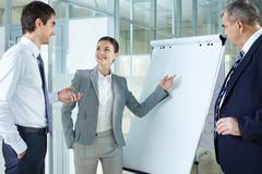 young woman presenting project to her colleagues - stock photo