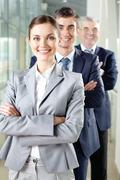 Smiling businesswoman looking at camera with two men behind Stock Photos