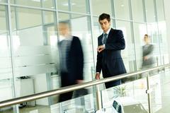 liikemies katsot kellosta kävely ihmisiä taustalla - stock photo