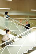photo of busy partners communicating while going upstairs in office building - stock photo