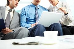 Three business people sitting on sofa and looking at laptop Stock Photos