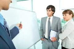 a group of colleagues looking at whiteboard while their employer explaining them - stock photo