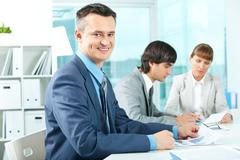 Successful businessman looking at camera in working environment Stock Photos